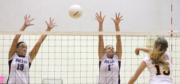 Mike Greene - mgreene@shawmedia.com Prairie Ridge's Alit Witt (left) and teammate Caitlin Brauneis attempt to block a shot from Jacobs' Jenna Bilgrien during the first set of a conference match Tuesday, September 18, 2012 at Prairie Ridge High School in Crystal Lake. Prairie Ridge (4-0) defeated Jacobs (3-1) in three sets to remain undefeated in the conference.