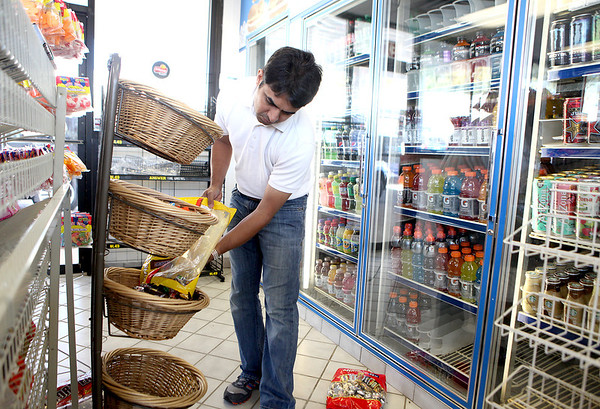 Co-owner Syed Irfan stocks candy at the Marathon gas station and convenience store at Routes 64 and 47 in Lily Lake Tuesday. The station had been shuttered for about four years.(Sandy Bressner Photo)