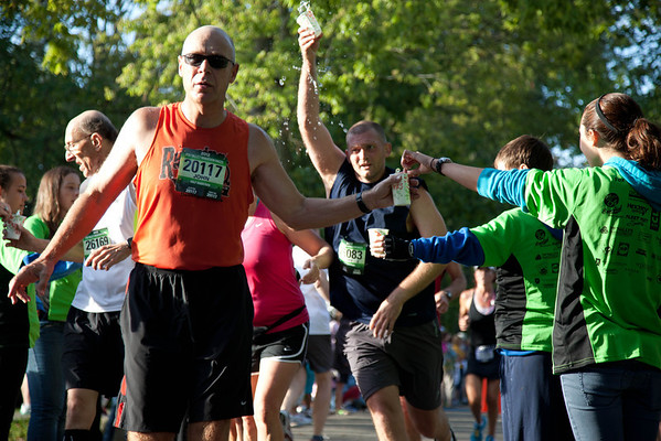 Volunteers of the Fox Valley Marathon cool off runners at Fabyan Forest Preserve Sunday morning in Geneva.