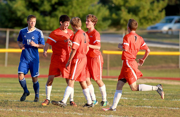 St. Charles East's Taylor Ortiz (second from left) celebrates with his teammates after a second-half goal during their Tri-City Shootout game against Geneva at East Tuesday evening.