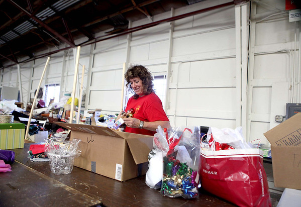 Roxanne Sronkoski of Geneva sorts through boxes of donated items to be sold this weekend during the annual St. Peter Barn Sale at the Kane County Fairgrounds in St. Charles.(Sandy Bressner photo)