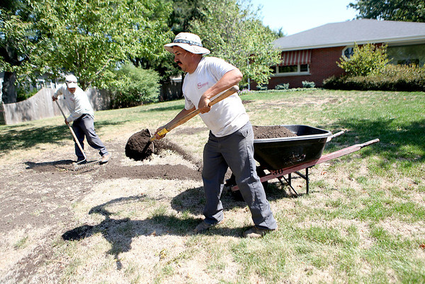 Victor Ramirez (right) and Elias Morales (left) of Thornapple Landscapes work on a yard on Meadows Road in Geneva Thursday.(Sandy Bressner photo)