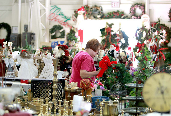 Judy Kropp of Geneva puts items ton display in preparation for this weekend's St. Peter Barn Sale at the Kane County Fairgrounds in St. Charles.(Sandy Bressner photo)
