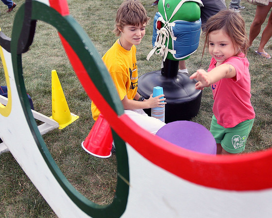 Sydney Cullen, 4, a resident of the Fox Mill Subdivision, punches the cup through the hole during Saturday's United Fall Fest at the Congregation United Church of Christ.<br />  (Jeff Krage photo for the Kane County Chronicle)