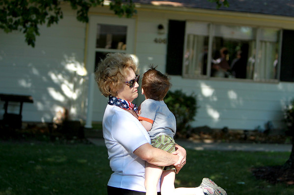 Jeanne Hope of St. Charles holds Oliver Roush, 4, who she babysits for, during a ceremony in honor of the anniversary of the 9/11 terrorist attacks. The ceremony was held in the front yard of Elburn resident Paul Wdowicki, who has planted a 9/11 memorial garden. Hope's daughter and son-in-law were near the twin towers in New York City during the attack.<br /> (Sandy Bressner photo)