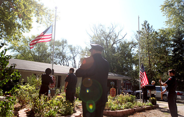 Members of the Elburn and Countryside Fire Protection District raise two American flags to half staff during a ceremony in honor of the anniversary of the 9/11 terrorist attacks. The ceremony was held in the front yard of Elburn resident Paul Wdowicki, who has planted a 9/11 memorial garden. (Sandy Bressner photo)