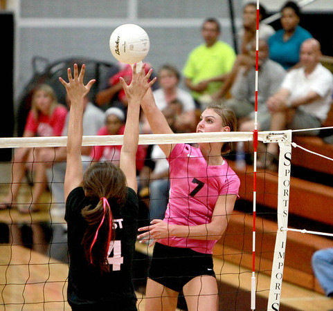 Taylor Krage of St. Charles North spikes the ball over the head of St. Charles East's Caitlyn Ballard during East's 25-21, 25-12 win Tuesday night. (Sandy Bressner photo)