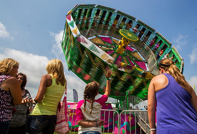 Kyle Grillot - kgrillot@shawmedia.com   Abbey Kent, 8, of Lake in the Hills (center) waves at friends on the Zero Gravity ride at the carnival Sunday, September 1, 2013, the last day of the Summer Sunset Festival. As Labor day symbolizes the end of summer many spectators come out to enjoy a few more summer activities.