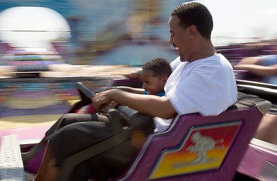 Kyle Grillot - kgrillot@shawmedia.com   Shaun Harold, and his son Shaun Harold Jr., 6, ride the Himalaya ride at the carnival Sunday, September 1, 2013, the last day of the Summer Sunset Festival. As Labor day symbolizes the end of summer many spectators come out to enjoy a few more summer activities.
