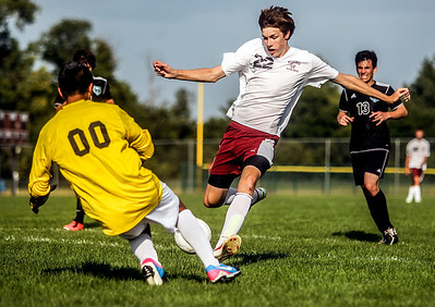 Sarah Nader -  snader@shawmedia.com Marengo's Nick Vanvorhees (right) runs into Woodstock North's goalie Ricky Rodriguez during the first half of  Wednesday's game at Marengo High School September 4, 2013. Woodstock North won, 4-3.