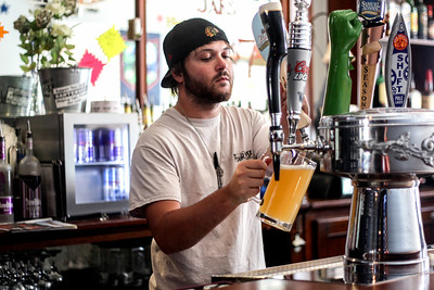 Sarah Nader -  snader@shawmedia.com Bartender Josh Lewellyn pours a beer while working at  PourHouse in Woodstock Thursday, September 5, 2013.