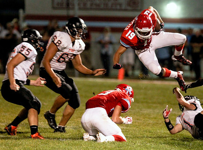 Sarah Nader -  snader@shawmedia.com Marian Central's Jordan Niemeyer jumps over a McHenry player while running a play during the first quarter of Friday's game against McHenry in Woodstock September 6, 2013. Marian Central defeated McHenry, 40-14.