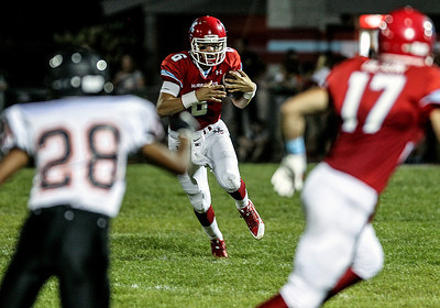 Sarah Nader -  snader@shawmedia.com Marian Central's quarterback Billy Bahl runs a play during Friday's football game against McHenry September 6, 2013. Marian Central defeated McHenry, 40-14.