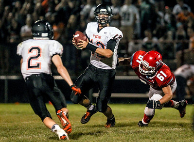 Sarah Nader -  snader@shawmedia.com McHenry's quarterback Mike Briscoe (center) is tackled by Marian Central's Josh Olsen during the third quarter of Friday's game in Woodstock September 6, 2013. Marian Central defeated McHenry, 40-14.