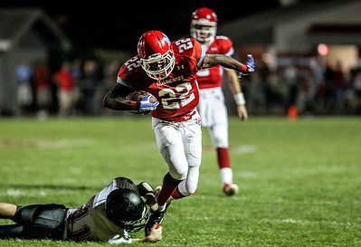 Sarah Nader -  snader@shawmedia.com Marian Central's Ephraim Lee (right) is tackled by McHenry's Thomas Hellios during the first quarter of Friday's game in Woodstock September 6, 2013. Marian Central defeated McHenry, 40-14.