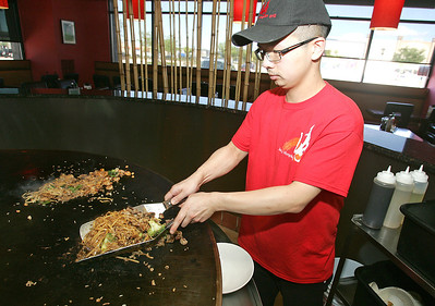 H. Rick Bamman -hbamman@shawmedia.com   Jiang's Mongolian Grill cook David Weng prepares a lunch order Friday, Sept. 13, 2013. The eatery opened late in 2012 at Algonquin Commons.