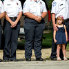 Lilly Hansen, 3, daughter of Elburn and Countryside Fire Protection District Lt. Matt Hansen looks on during a remembrance ceremony commemorating the 12th anniversary of the 9/11 attacks at the Elburn home of Paul Wdowicki Wednesday morning.