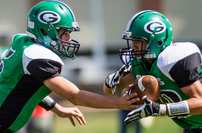 Kyle Grillot - kgrillot@shawmedia.com   Alden-Hebron sophomore Colten Cashmore (left) hands the ball off to sophomore Nate Peterson during the first quarter of the football game against Chicago Hope at Alden-Hebron Saturday, September 14, 2013. Alden-Hebron lost to Chicago Hope 31-21.