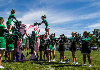 Kyle Grillot - kgrillot@shawmedia.com   Alden-Hebron sophomore Nate Peterson leads his team through a paper banner before the start of the football game against Chicago Hope at Alden-Hebron Saturday, September 14, 2013. Alden-Hebron lost to Chicago Hope 31-21.