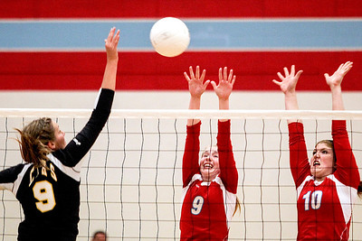 Sarah Nader -  snader@shawmedia.com Marian Central's Alex Kaufmann (left) and Rachel Giustino jump to block a ball hit by Chicago Christian's Jessica Krygsheld during Monday's match in Woodstock September 16, 2013. Marian Central was defeated, 0-2.