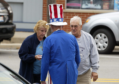 Barb Soracco of Huntley and Bill Norberg of Mt.Prospect are greeted by  Uncle Sam portrayed by Jim Nelson prior to the start of the Huntley  Constitution Day program Tuesday at the Huntley Square Gazebo on Main Street. Those gathered joined in the Pledge of Allegiance and the reading of the preamble to the Constitution. H. Rick Bamman - hbamman@shawmedia.com
