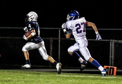 Sarah Nader- snader@shawmedia.com Cary-Grove's Larkin Hanselmann (left) is guarded by Dundee-Crown's Fabian Guttierez during the third quarter of Friday's football game In Cary September 20, 2013. Cary-Grove defeated Dundee-Crown, 34-0.