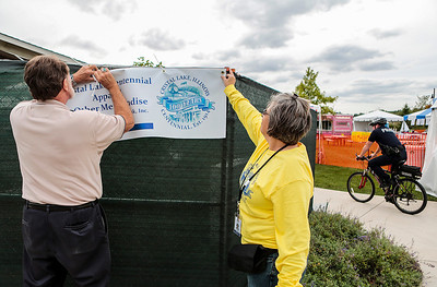 Kyle Grillot - kgrillot@shawmedia.com   Fred Kaiser (left) is helped by Carrie Futchko while putting up a sign at the Crystal Lake Centennial Kick-Off Festival at Three Oaks Recreation Area Friday, September 20, 2013. The festival is part of the celebration of the 100th birthday since Crystal Lake's incorporation as a city, and will continue until Sunday at 6 p.m.