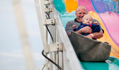 Kyle Grillot - kgrillot@shawmedia.com   Tom Smith holds Cameron Smith, 1, as they slide down the Fun Slide during the Crystal Lake Centennial Kick-Off Festival at Three Oaks Recreation Area Friday, September 20, 2013. The festival is part of the celebration of the 100th birthday since Crystal Lake's incorporation as a city, and will continue until Sunday at 6 p.m.