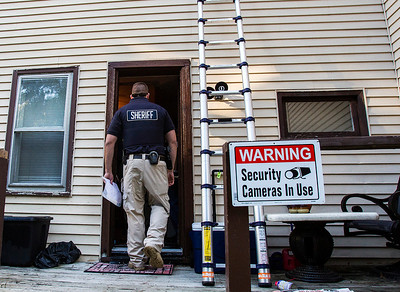 Kyle Grillot - kgrillot@shawmedia.com   Drug dealers are commonly known to install surveillance systems on their home. A police officer enters the suspects home on Jackson Street in Woodstock Thursday September 26, 2013. At least 35 officers from Woodstock, Lake in the Hills, McHenry Sheriffs department, and the U.S. Marshall's Great Lakes Regional Fugitive Task Force went to 20 different locations around McHenry county Thursday morning to arrest suspects with drug-related felony warrants. These types of criminal roundups are clustered together in order to use these resources in a cost effective manner. Today, 16 of the 20 warrants ended in arrests, and at least 10 will now have additional charges based on the recovery of paraphernalia and other charges.