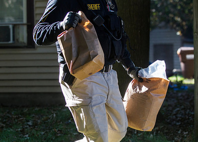 Kyle Grillot - kgrillot@shawmedia.com   A police officer carries contraband to be used as evidence from a home on Jackson Street in Woodstock Thursday September 26, 2013. At least 35 officers from Woodstock, Lake in the Hills, McHenry Sheriffs department, and the U.S. Marshall's Great Lakes Regional Fugitive Task Force went to 20 different locations around McHenry county Thursday morning to arrest suspects with drug-related felony warrants. These types of criminal roundups are clustered together in order to use these resources in a cost effective manner. Today, 16 of the 20 warrants ended in arrests, and at least 10 will now have additional charges based on the recovery of paraphernalia and other charges.