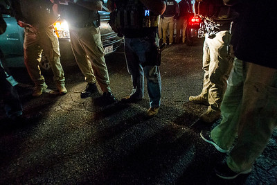 Kyle Grillot - kgrillot@shawmedia.com   Just after 5 a.m., police gather to listen to a U.S. Marshall's debriefing Thursday September 26, 2013. A large amount of man-power is required for an operation like the roundup that takes place soon after the debriefing. For the safety of the officers, some of whom work undercover, their faces are kept out of the images. At least 35 officers from Woodstock, Lake in the Hills, McHenry Sheriffs department, and the U.S. Marshall's Great Lakes Regional Fugitive Task Force went to 20 different locations around McHenry county Thursday morning to arrest suspects with drug-related felony warrants. These types of criminal roundups are clustered together in order to use these resources in a cost effective manner. Today, 16 of the 20 warrants ended in arrests, and at least 10 will now have additional charges based on the recovery of paraphernalia and other charges.