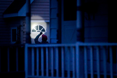 Kyle Grillot - kgrillot@shawmedia.com   A U.S. Marshall shines his flashlight into the door of a suspect's home on Hoy Avenue in Woodstock Thursday September 26, 2013. At least 35 officers from Woodstock, Lake in the Hills, McHenry Sheriffs department, and the U.S. Marshall's Great Lakes Regional Fugitive Task Force went to 20 different locations around McHenry county Thursday morning to arrest suspects with drug-related felony warrants. These types of criminal roundups are clustered together in order to use these resources in a cost effective manner. Today, 16 of the 20 warrants ended in arrests, and at least 10 will now have additional charges based on the recovery of paraphernalia and other charges.