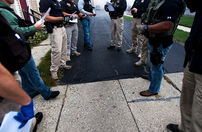 Kyle Grillot - kgrillot@shawmedia.com   Police gather on Hoy Avenue in Woodstock to listen to a U.S. Marshall's debriefing after an arrest, and before moving to the next location. A debriefing takes place before every arrest to be sure that all members of the team know what the suspect looks like, as well as any other important information pertinent to the arrest. Thursday September 26, 2013. At least 35 officers from Woodstock, Lake in the Hills, McHenry Sheriffs department, and the U.S. Marshall's Great Lakes Regional Fugitive Task Force went to 20 different locations around McHenry county Thursday morning to arrest suspects with drug-related felony warrants. These types of criminal roundups are clustered together in order to use these resources in a cost effective manner. Today, 16 of the 20 warrants ended in arrests, and at least 10 will now have additional charges based on the recovery of paraphernalia and other charges.