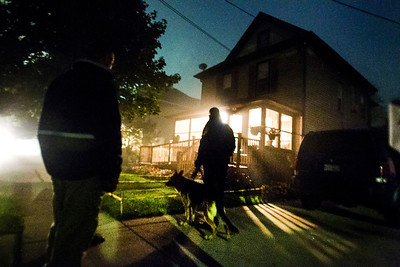Kyle Grillot - kgrillot@shawmedia.com   A U.S. Marshall shines his flashlight into the door of a home on Hoy Avenue in Woodstock Thursday September 26, 2013. At least 35 officers from Woodstock, Lake in the Hills, McHenry Sheriffs department, and the U.S. Marshall's Great Lakes Regional Fugitive Task Force went to 20 different locations around McHenry county Thursday morning to arrest suspects with drug-related felony warrants. These types of criminal roundups are clustered together in order to use these resources in a cost effective manner. Today, 16 of the 20 warrants ended in arrests, and at least 10 will now have additional charges based on the recovery of paraphernalia and other charges.