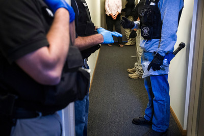 Kyle Grillot - kgrillot@shawmedia.com   Holding recovered paraphernalia, police officers guide a suspect out of her apartment in the Willow Brooke Apartments in Woodstock Thursday September 26, 2013. Because of various health concerns related to heroin users, officers must wear gloves, as well as other precautions, while searching a suspect's home. Some suspects have such bad cases of MRSA that roundups like these are not adequately safe for officers to make an arrest, and other actions are then required. At least 35 officers from Woodstock, Lake in the Hills, McHenry Sheriffs department, and the U.S. Marshall's Great Lakes Regional Fugitive Task Force went to 20 different locations around McHenry county Thursday morning to arrest suspects with drug-related felony warrants. These types of criminal roundups are clustered together in order to use these resources in a cost effective manner. Today, 16 of the 20 warrants ended in arrests, and at least 10 will now have additional charges based on the recovery of paraphernalia and other charges.