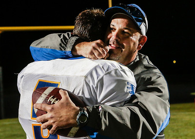 Kyle Grillot - kgrillot@shawmedia.com   Johnsburg junior quarterback Nick Brengman hugs Dan Stefka, father of junior Bailey Stefka after winning the high school football game against Woodstock North High School Friday, September 27, 2013. Johnsburg won the game, ending a 25 game losing streak.
