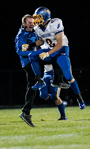 Kyle Grillot - kgrillot@shawmedia.com   Johnsburg senior Steve Dixon (2) celebrates with a member of the coaching staff after running the ball in for a touchdown in the during thesecond quarter of the high school football game at Woodstock North High School Friday, September 27, 2013. Johnsburg won the game, ending a 25 game losing streak.