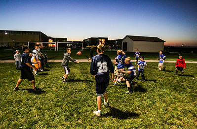 Kyle Grillot - kgrillot@shawmedia.com   Kids pass a football next to the football field at at Woodstock North High School during the football game Friday, September 27, 2013. Johnsburg won the game, ending a 25 game losing streak.