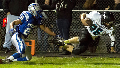 Brett Moist/ for the Northwest Herald   Woodstock North's Alex Mitchell dives past Woodstock's Ashton Bracy into the endzone for the touchdown during the 2nd quarter of gameplay against Woodstock North at Woodstock High School on Friday.