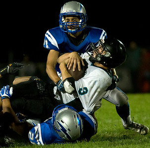 Brett Moist/ for the Northwest Herald   Woodstock North's Jimmy Krenger (3) gets tackled by Tim Piquette (top) and Ashton Bracy (bottom) during the 3rd quarter of gameplay against Woodstock North at Woodstock High School on Friday. Billy Darling (83) helped block for Jimmy Krenger.