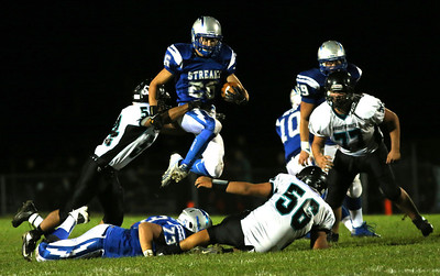 Brett Moist/ for the Northwest Herald   Woodstock's Alex Shannon jumps over fallen teammate, Langdon Scoot during the 3rd quarter of gameplay against Woodstock North at Woodstock High School on Friday. Woodstock North's Marcos Carbajal (left), Brendan Domek (middle), and John Ison (right) were there for the stop.