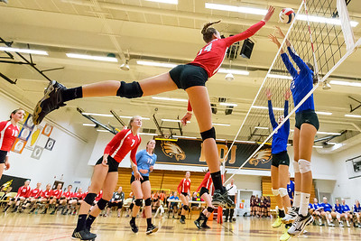Marion Central Catholics' Lauren Hanlon (14) flies high above the net against the defenders from Catholic Memorial Saturday, Sept 3rd at the Jacob Varsity Volleyball Innovational held at Jacobs High School in Algonquin. Marion went on to take first place in the tournament. Ken Koontz – For Shaw Media