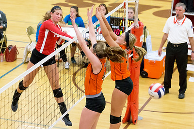 Marion Central Catholics' Sydney Nemtuda (10) goes over the top of Crystal Lake Central defenders Megan Kelly (42) and Madelyn Blake (35) Saturday, Sept 3rd at the Jacob Varsity Volleyball Innovational held at Jacobs High School in Algonquin. Marion went on to take first place in the tournament. Ken Koontz - For Shaw Media
