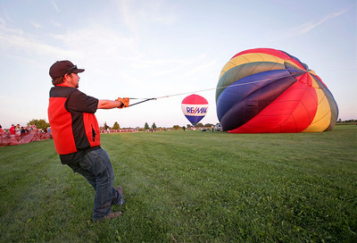 Bret Wiley helps steady a hot air ballon as they attempt to inflate it for the Balloon Night Glow at the inaugural Harvard Balloon Fest on Saturday, September 3, 2016 in Harvard, Ill. John Konstantaras photo for the Northwest Herald