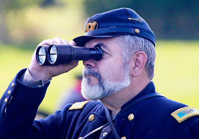Candace H. Johnson-For Shaw Media Gerry Morin, of Antioch, a Union general with the Illinois Battalion, looks through his binoculars while his men fight in a skirmish during the Civil War Re-Enactment and Battle at the Northbrook Sports Club in Hainesville.