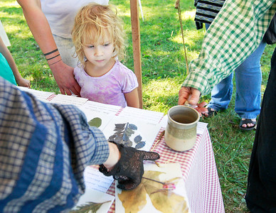 Candace H. Johnson-For Shaw Media Daisy Snow, 4, of Lindenhurst learns about different plants used during the Civil War including chicory root which was used to make coffee during the Civil War Re-Enactment and Battle at the Northbrook Sports Club in Hainesville.