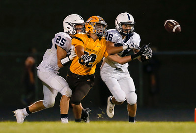 David Daigle (25) and Matt McQuade (26) of Cary-Grove break up a pass intended for Cole Patrician (82) from Jacobs during the fourth quarter of their game at Jacobs High School on Friday, September 16, 2016 in Algonquin. The Trojans defeated the Golden Eagles 35-14.  John Konstantaras photo for the Northwest Herald