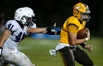 Quarterback Christopher Katrenick (2) from Jacobs is chased out of bounds by Jacob Kuhl (41) of Cary-Grove and Daniel Gajewski (54) during the second quarter of their game at Jacobs High School on Friday, September 16, 2016 in Algonquin. The Trojans defeated the Golden Eagles 35-14.  John Konstantaras photo for the Northwest Herald