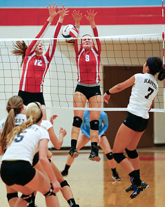 Rachel Noonan (12) and Brenna Koch (9) of Marian Central Catholic jump to block a hit by Jimena Montano (7) of Harvest Christian during their first game at Marian Central Catholic High School on Monday, September 19, 2016 in Woodstock, Ill. The Hurricanes defeated the Lions in 2 games; 25-16, 25-19.  John Konstantaras photo for the Northwest Herald