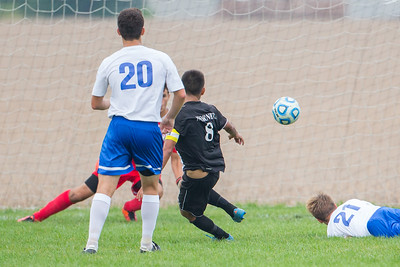 Harvard team captain Alfredo Pichardo (8) drives between Johnsburg defenders Will Conroy (20) and Keith Adamkiewicz (21) for the goal Saturday, Sept. 24th 2016 at Johnsburg High School. Harvard went on to defeat Johnsburg by a score of 3-1. KKoontz – for Shaw Media